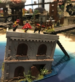 The archers take up a vantage point on a wrecked building, with Hugo de Moncada offering moral support.
